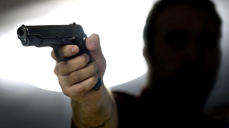 Tumma hahmo osoittaa aseella kameraa kohti.