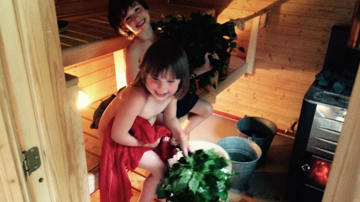 Kaksi iloista lasta puulämmitteisessä saunassa vihtomassa