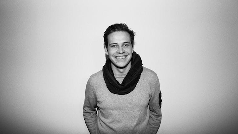 Mustavalkoinen kuva hymyilevästä collegepaitaisesta Janne Sarjasta.