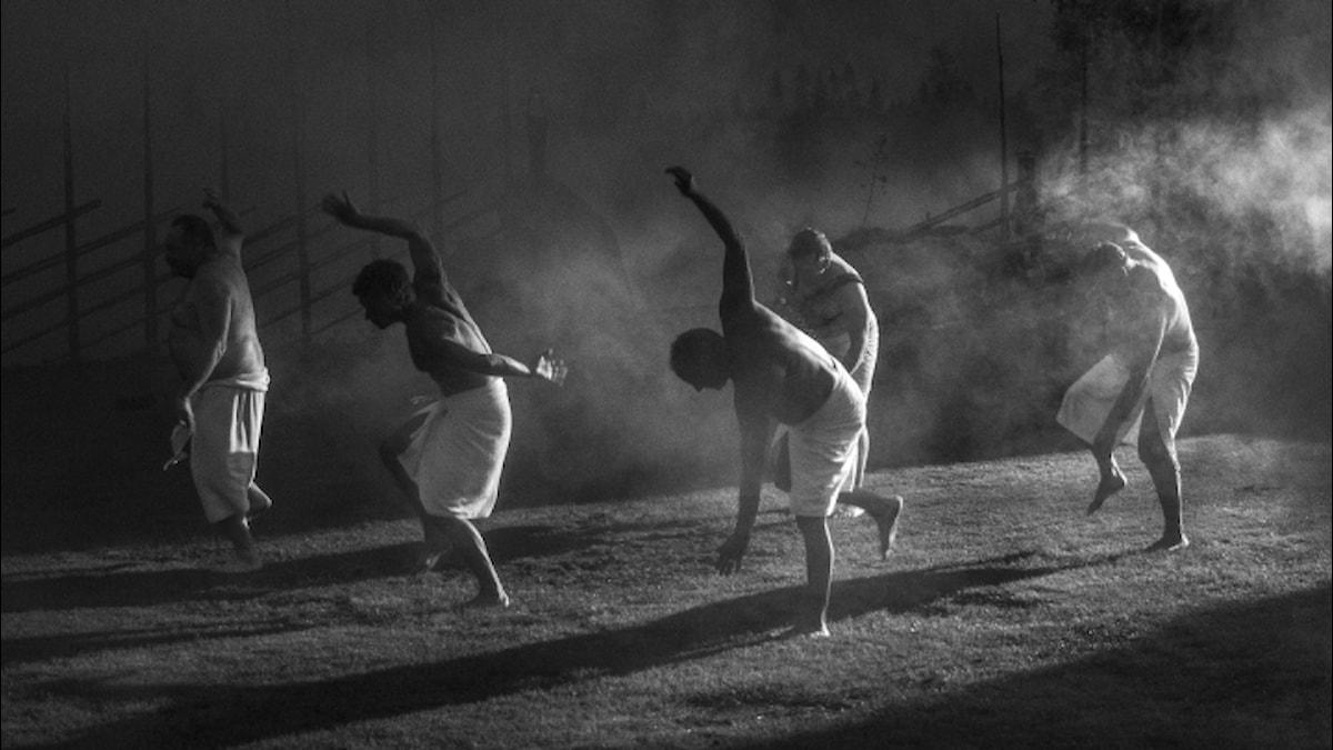 Mustavalkoisessa kuvassa viisi höyryävää miestä, joilla valkoiset pyyhkeet lanteilla, muuten alasti, tanssii yöllä nurmkiolle tulevassa valokiilassa.
