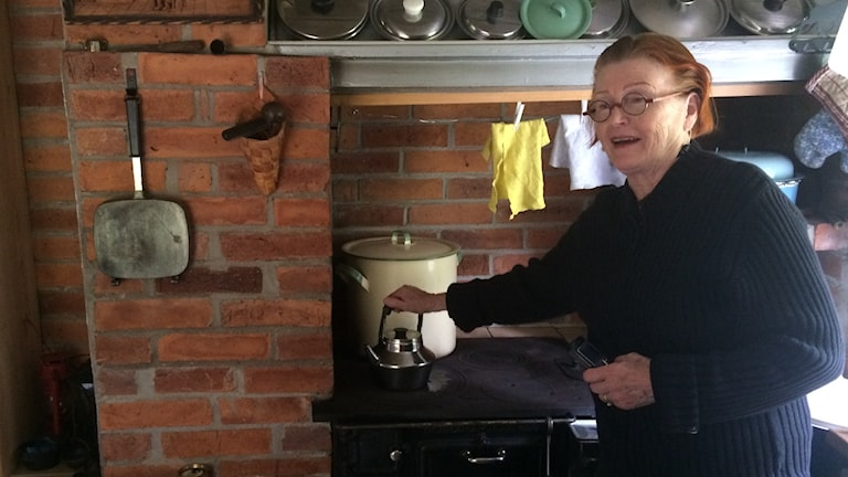 Kaarina Lindell Lignell torppansa keittiössä, kahvipannu puuhellalla kiehumassa