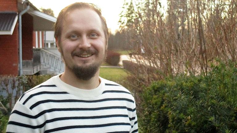 Janne Hämeenniemi kotipihallaan, mustaraitainen valkea pusero yllään.