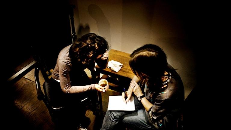 På bilden sitter två kvinnor och samtalar med varann i ett litet rum.