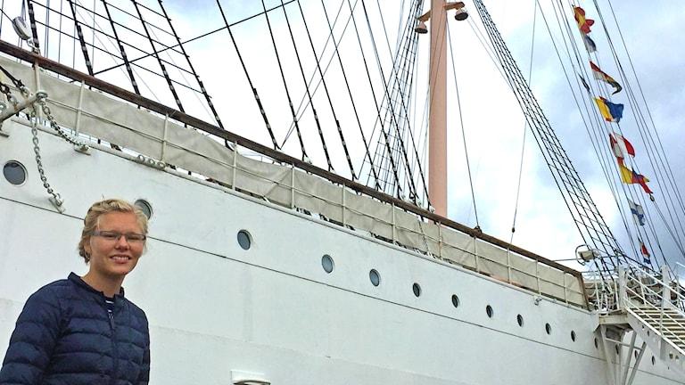 En blond tjej står framför ett stort vitt segelfartyg