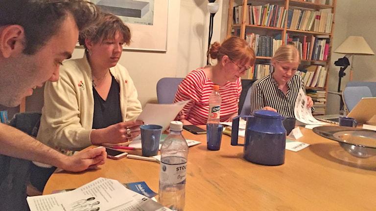 Suomen kielen opintopiirin osallistujia ja vetäjä papereineen ja kahvikuppeineen pöydän äärellä.