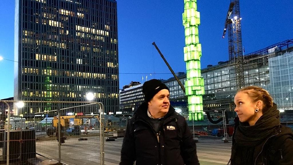 Keijo Knutas ja Hanna Hallakumpu seisovat Sergelin torilla suihkulähteen loistaessa vihreänä taustalla.
