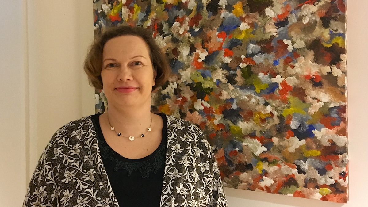 Lundissa asuva Pia Ukkonen seisoo värikkään taustan edessä.