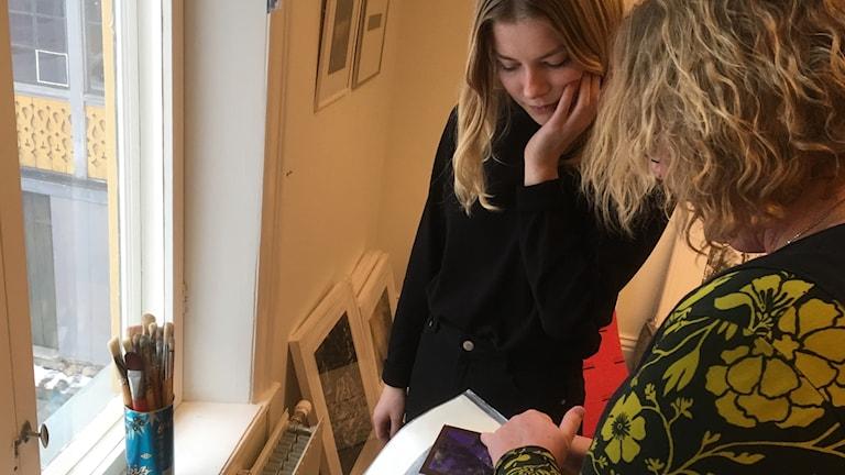 Erja Tienvieri ja tyttärensä Julia Erjan ateljeessa tarkastelemassa grafiikkalevyä, seinustoilla tauluja