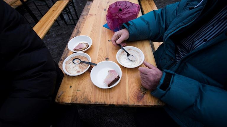 Kuvassa näkyy kaksi koditonta miestä syömässä.
