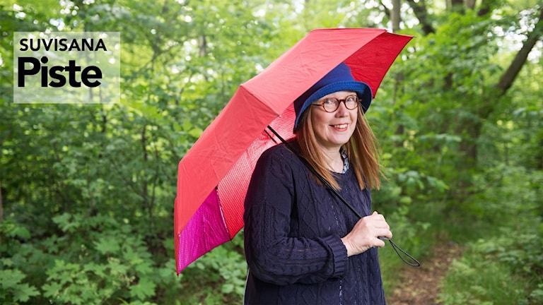 Riitta Niemi punaisen sateenvarjon alla keväisen vihreässä metsässä.