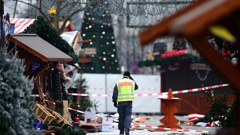 Yksinäinen poliisi kävelee keskellä hajalla olevia myyntikojuja joulumarkkinoilla Berliinissä.