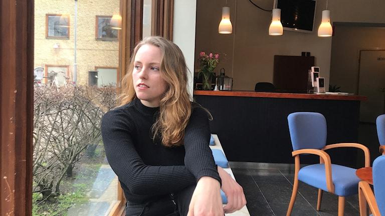 Nuori nainen (Sonia Haga) istuu ikkunalla ja katsoo ulospäin.