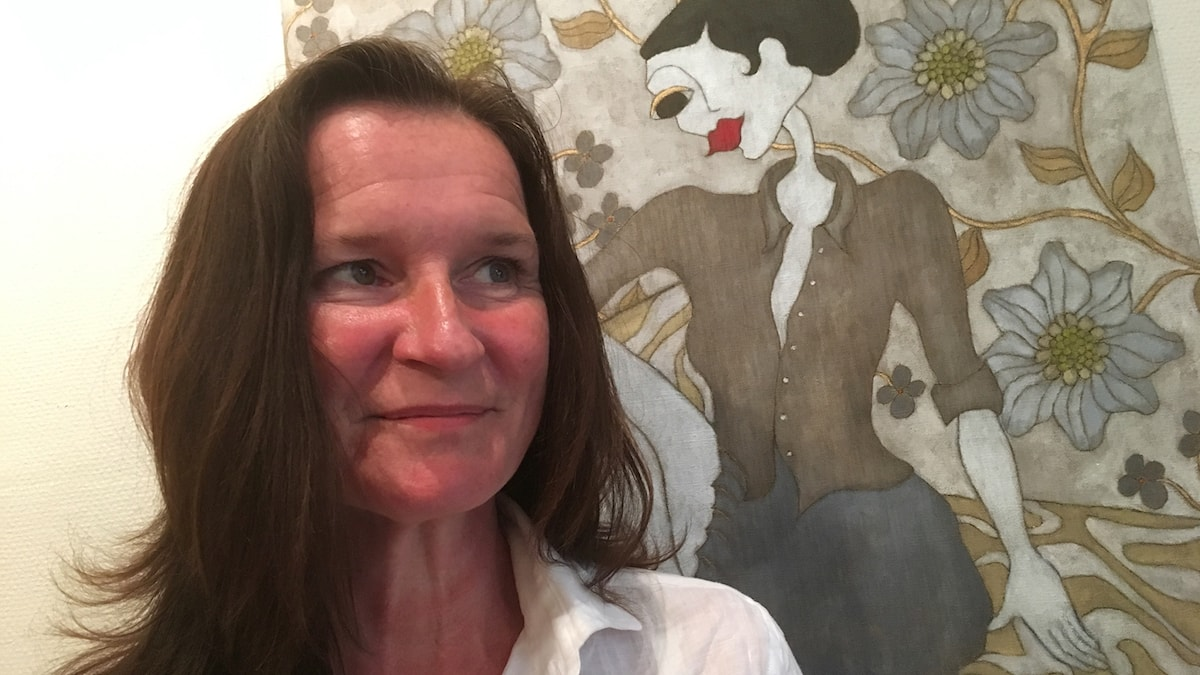 Reija Karjalainen yksisilmäistä naista esittävän maalauksensa edessä.
