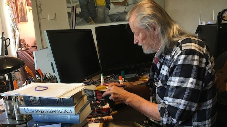 Ruutupaitainen kirjailija istuu sammutettujen tietokoneidensa ääressä kirjoja selaten