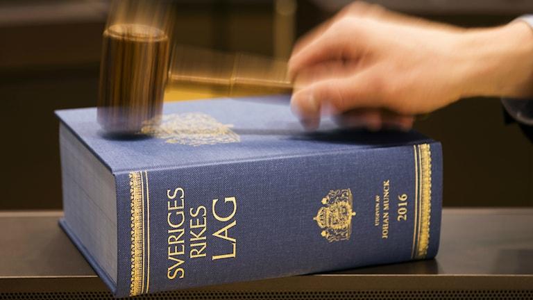 Kuvituskuva. Pöydällä Ruotsin laki -kirja, käsi kopauttaa nuijalla päälle.