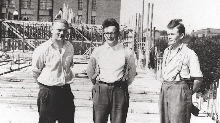 Kolme miestä suomalaisella rakennustyömaalla 1950-luvulla.