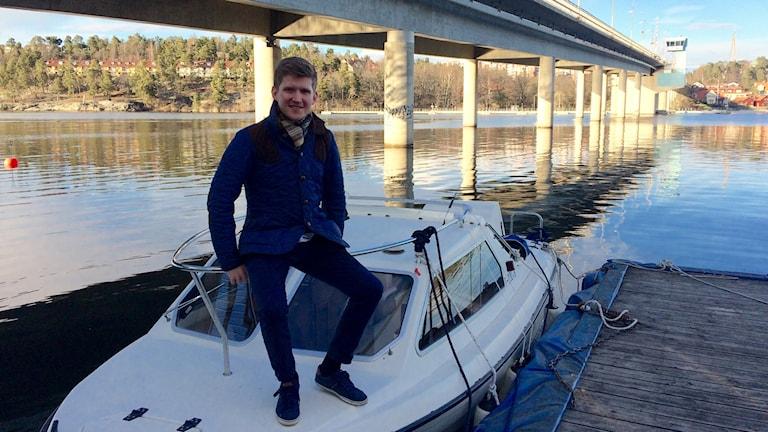 Moritz Kåla istuu isänsä moottoriveneen kaiteella. Taustalla silta.