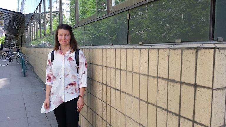 Noora Aakko seisoo ohut kukallinen pusero tuulessa heiluen likaisen seinän vieressä taustalla aurinko ja kesäiset puut heijastuvat taon ikkunoihin.