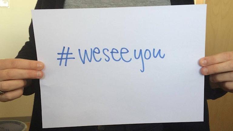 En person håller upp en lapp med hashtag we see you