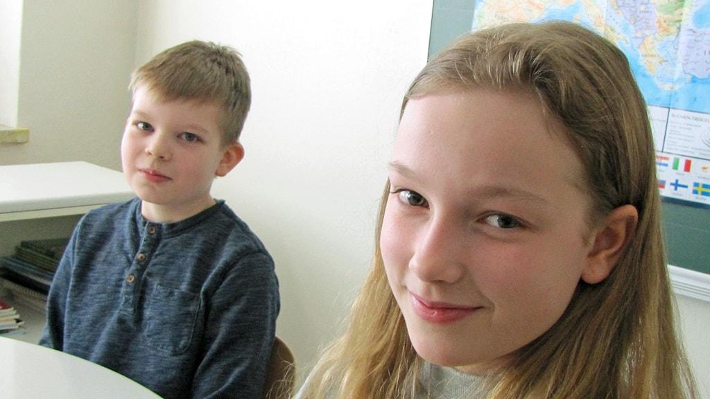 Kaksi peruskoululaista istuu pöydän ääressä lähikuvassa, poika ja tyttö.