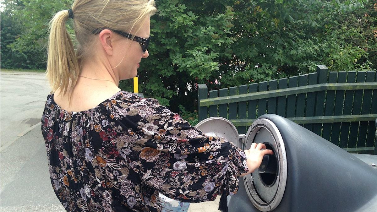 Nainen heittää lasin lasia varten tarkoitettuun kierrätyssäiliöön.