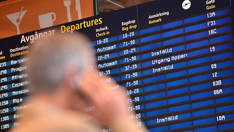 Taustalla Arlandan lentokentän lähtevien lentojen ilmoitustaulu ja edessä kännykkään puhuva epätarkka mieshahmo.
