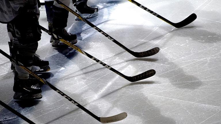 Ishockeyspelare står med klubbor