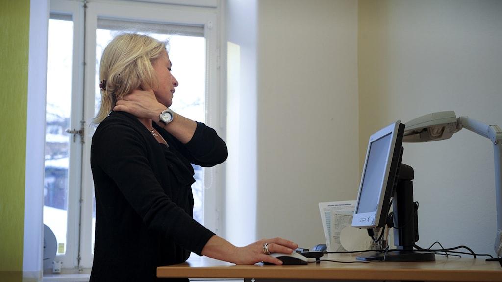 Hon tar sig för axeln, står vid arbetsbordet.