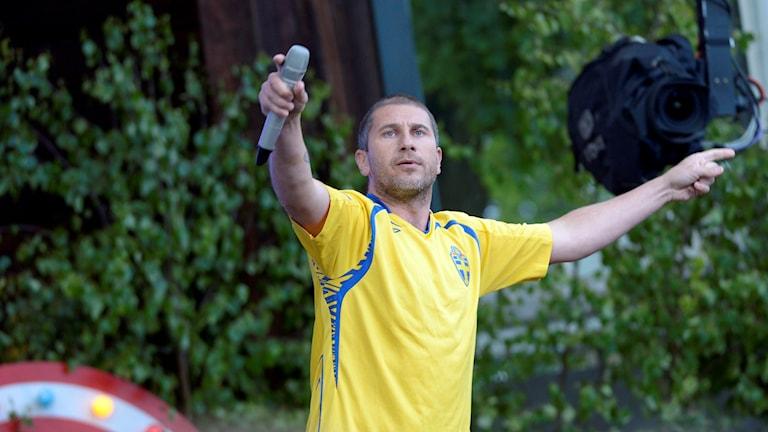 Artisti Markoolio esiintyy Allsång på Skansen-tapahtumassa Ruotsi-paita päällään.