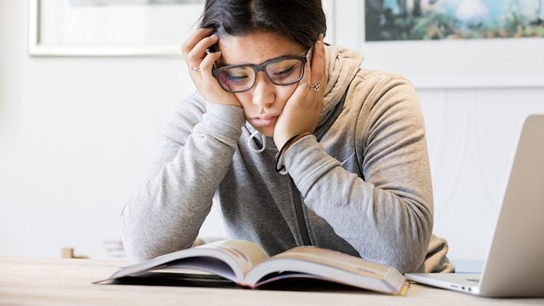 nainen lukee läksykirjaa