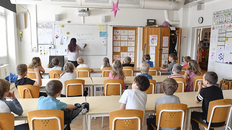 Ett klassrum fotograferat bakifrån. Elever sitter vid sina bänkar och tittar på läraren som skriver något på tavlan längst fram i klassrummet.