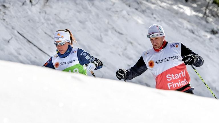 Kvassa etualla lumipenkka, jonka takaa näkyvät hiihtäjät Charlotte Kalla ja hänen vömentajansa Magnus Ingensson. Kuva:Anders Wiklund