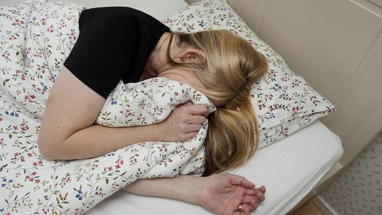 Kuvassa nainen makaa sängyssä pitäen peittoa osittain naamallaan.