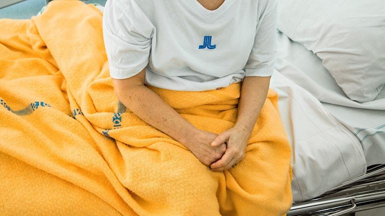 Kuvassa potilas istuu sängyllä kädet ristissä.