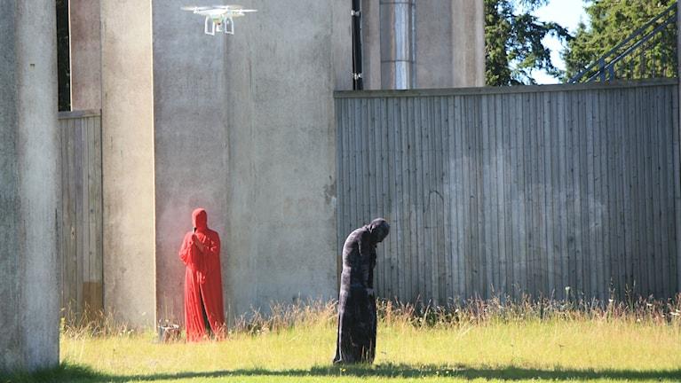 Jutta Annala punaisissaan ja Raisa Punkki mustissa esittävät vaikuttavaa performanssia Haaparannan vesitornilla. Pauliina Punkki ohjaa kopterikameraa.