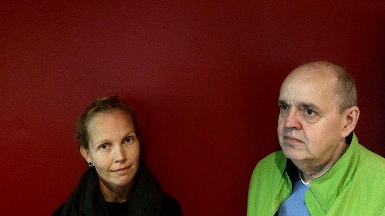 Lukupiiriläiset Hanna Hallakumpu ja Keijo Knutas punaisen seinän edessä.