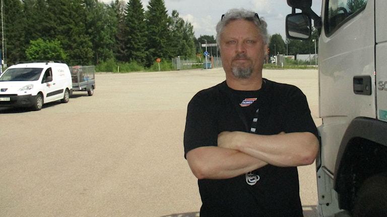 Erkka Petäjä kädet puuskassa ulkona, kuorma-auton vieressä.