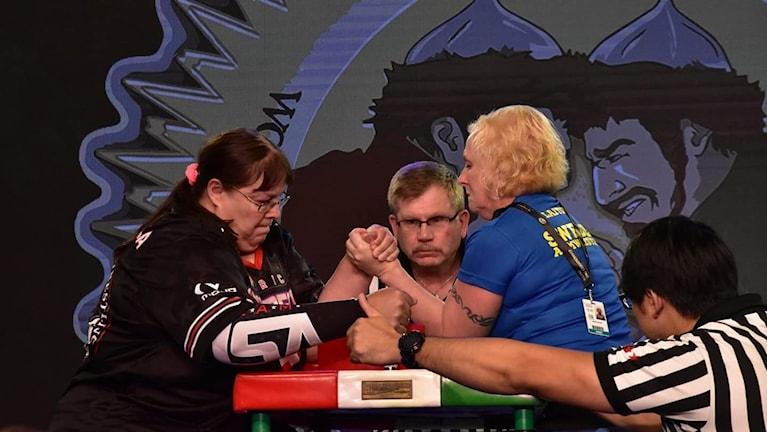 Kuvassa tumma- ja vaaleahiuksinen nainen vääntävät kättä tuomarien ympäröimänä.