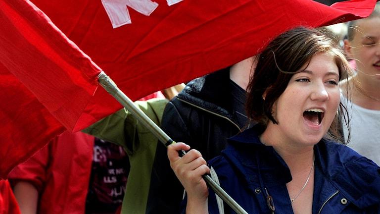 Punalippua kantava tyttö vappumarssilla