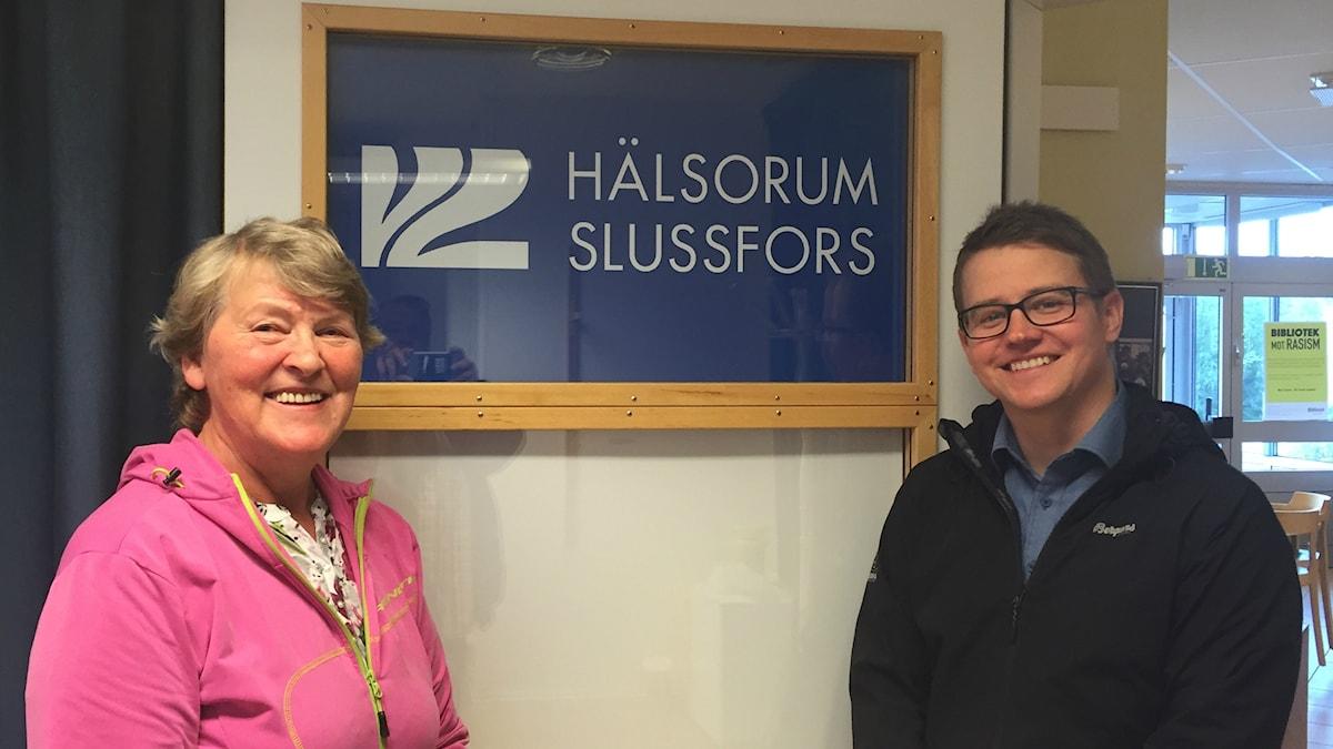 Vasemmalla Anneli Stenzelius vaaleanpunaisessa puserossaan, oikealla Andreas Lundqvist tummassa asussaan, välissä kyltti Hälsorum Slussfors.