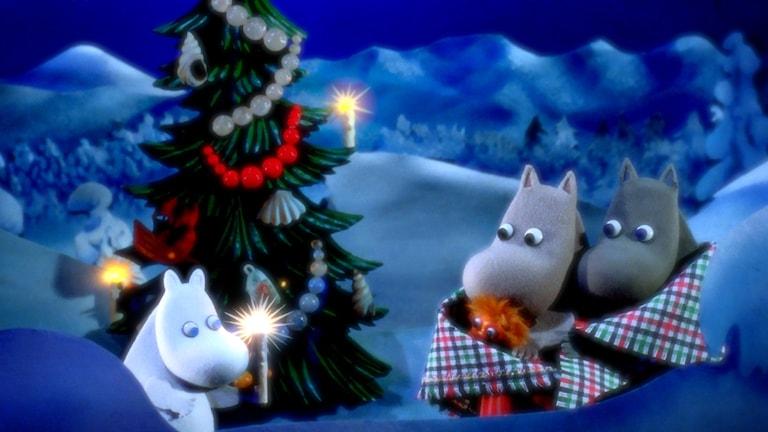 Kuvassa Muumi-perhe odottelee joulukuusen luona.