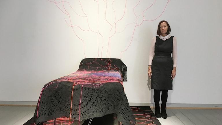 Taitelija Rita Pyy seisoo kuvassa oikealla, vasemmalla on hänen teioksensa Nattlig analys, jossa on sänky, jolla musta virkatuista liinoista tehty peitto. Sen päälle on punaisilla nauhoilla piirrettu Venäjän puoleisen Karjalan kartta. Rajaviivat jatkuvat seinälle ja lattialle. Kuva: Riitta Niemi/ Sveriges Radio Sisuradio.