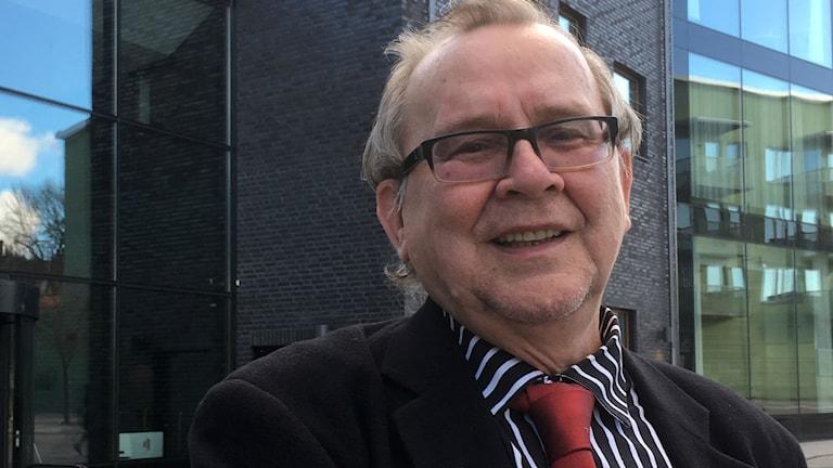 Kirjailija Leo Ylitalo seisoo lähikuvassa erittäin tummatiilisen talon edessä. Kuva: Riitta Niemi/ Sveriges Radio Sisuradio