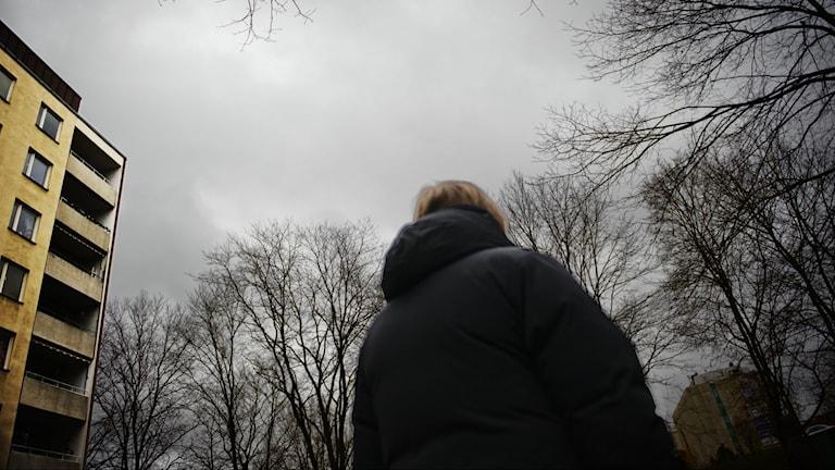 """Nainen seisoo seläten ja katsoo puita. """"Ihmiset haluaa aina syyn että miksi lyödään, mutta sitä ei ole. Se on niitten omassa päässä se syy"""", sanoo Maija."""