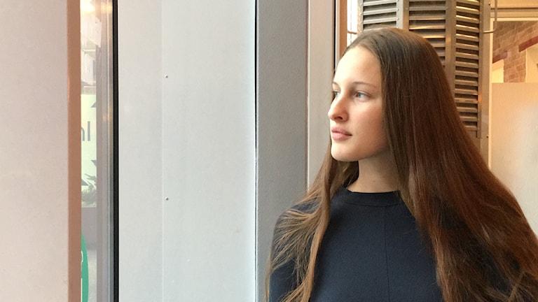 I bilden ser vi Sofia Kornesjö som tittar ut genom fönstret.