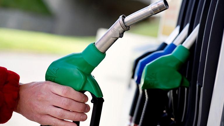 en man som håller i en bensinpump