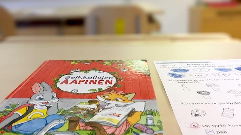 En bok och övningar på ett bord i ett klassrum.