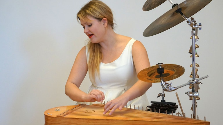 Maija Kauhanen soittaa valkeassa mekossa kannelta.
