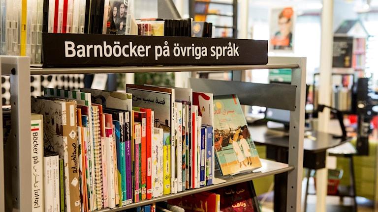 """Kuvassa kirjahylly kirjastossa ja osasto """"lastenkirjoja muilla kielillä""""."""