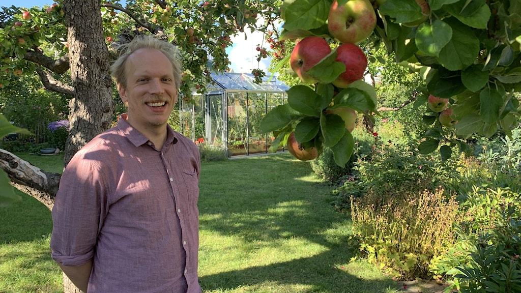 Nikolai Äystö seisoo omenapuun alla ja hymyilee.